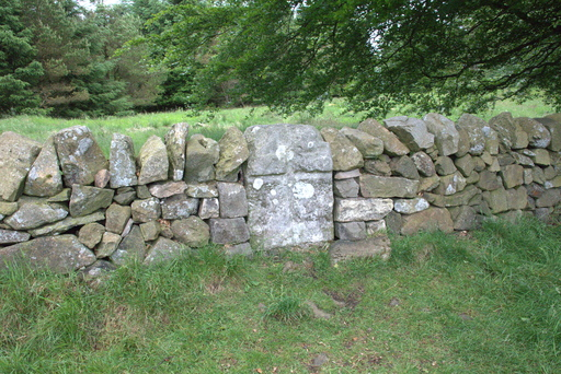 A stone with a cross built into a drystone dyke